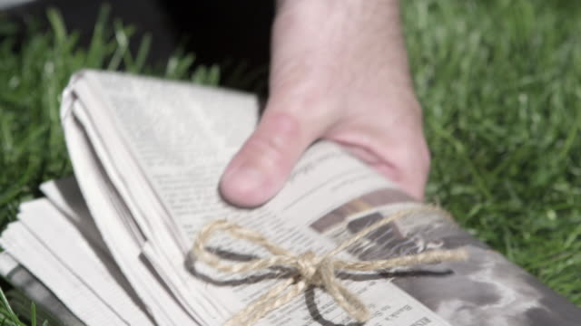 Close up of man picking morning newspaper off lawn