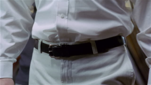 Close up of man unbuckling his belt and taking off his pants