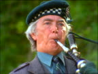 close up of man walking while playing bagpipes outdoors / Birnam, Scotland