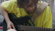 Close up of man with beard playing guitar / Hallstatt, Austria