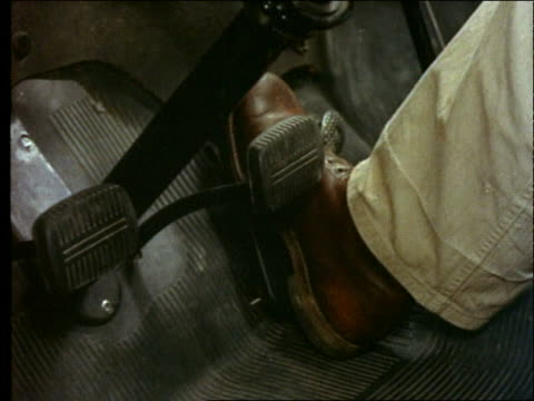 1955 close up of man's foot moving from gas pedal to brake / car
