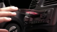 Close up of man's hand inserting compact disc into car stereo / adjusting volume / pressing play