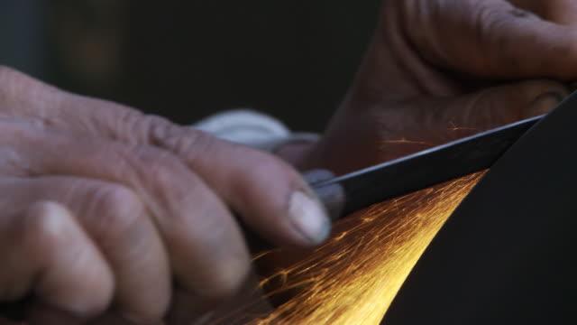 Close up of mans hands sharpening knife