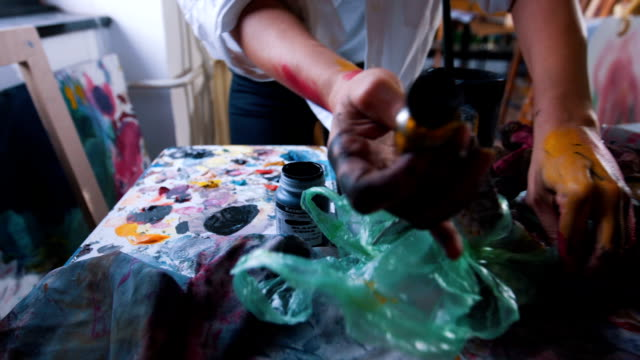 Close up of messy artist mixing oil colors