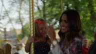 Close up of mother and daughter riding carousel at carnival / American Fork, Utah, United States