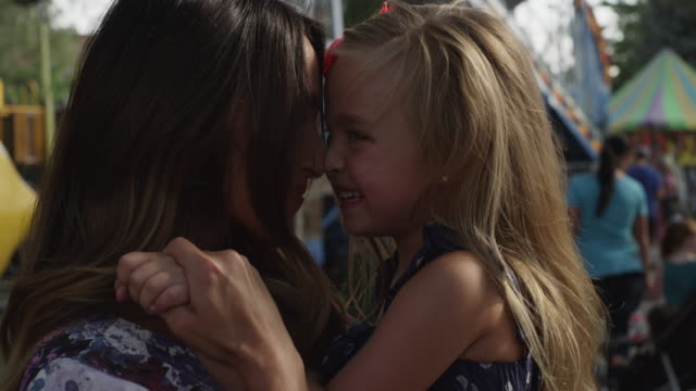 Close up of mother and daughter rubbing noses at carnival / American Fork, Utah, United States