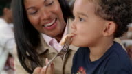 Close up of mother feeding pizza to son sitting on lap in pizza restaurant