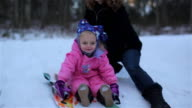 Close up of mother pushing her young daughter down a hill on a snow sled