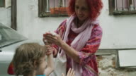 Close up of mother wiping hand of son in street / Plovdiv, Bulgaria