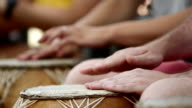 Close up of people playing hand drums in Ghana