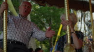 Close up of senior couple riding carousel at carnival / American Fork, Utah, United States