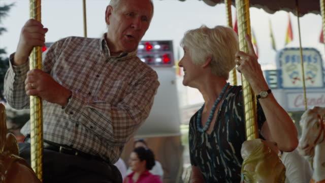 Close up of senior couple riding carousel at carnival / American Fork, Utah, United States