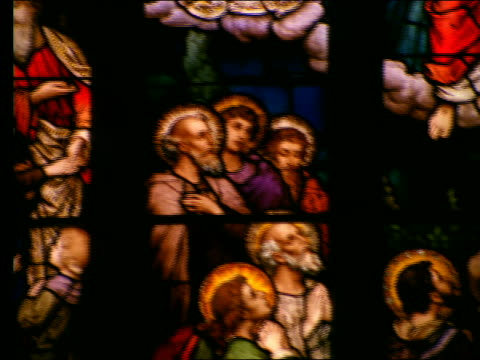 close up of stained glass window with religious scene