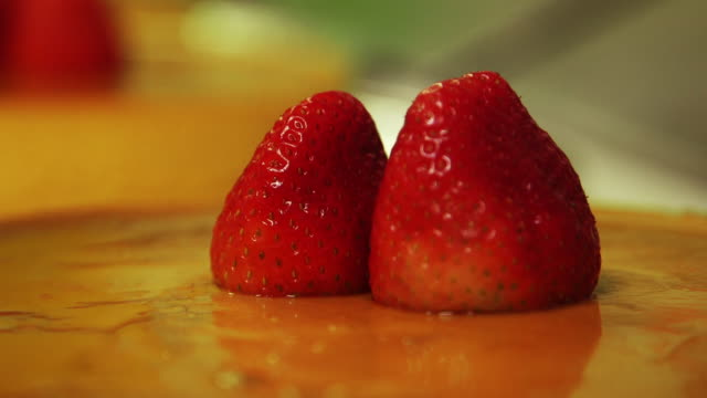 Close up of Strawberry flan person slices apple in background