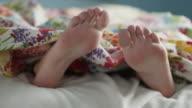Close up of teenage girls feet dancing under blanket / Sandy, Utah, United States
