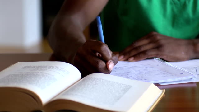 Close Up of Teen's Hands Writing Homework Assignment