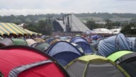 Close up of tents at the festival with the main stage in the background