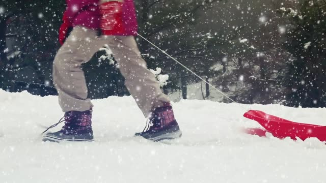 Close up of the feet of a girl walking thru the snow with a sled.