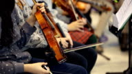 Close up of the hands of a girl with a violin in a group music class waiting to play