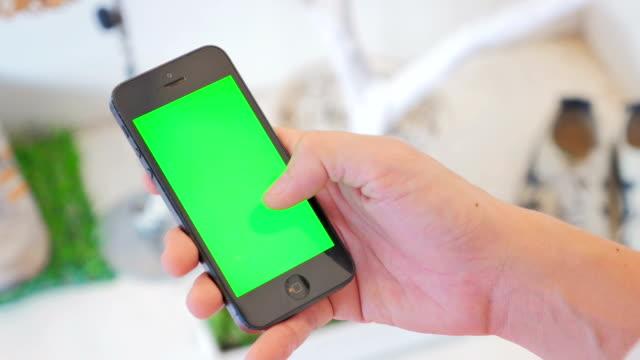 Primo piano di utilizzando uno smartphone, schermo verde