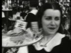 B/W close up of waitress carrying tray of food / Paris, France