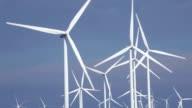 Close up of wind turbines in blue sky
