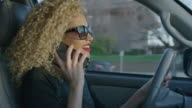 Close up of woman driving car and talking on cell phone / Provo, Utah, United States