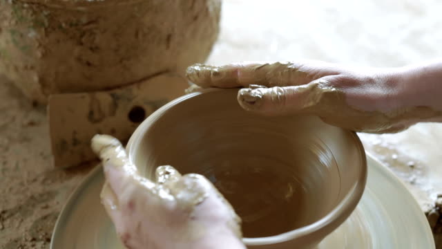 Close up of woman hands working on clay mud