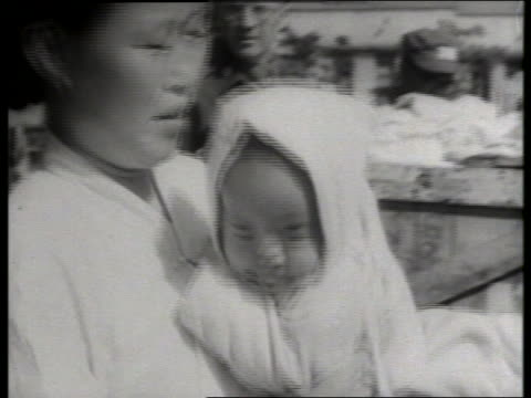 B/W close up of woman holding baby in bonnet / Korea / NO