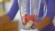 Close up of woman making fruit smoothie in kitchen