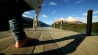 Nahaufnahme von Frau die Füße zu Fuß auf Holzsteg über See