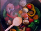 close up of wooden spoon stirring shrimp and vegetable stir-fry