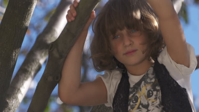 Close up of young girl with sad expression in a tree