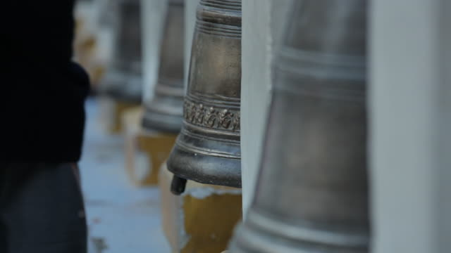 Close up of young man hitting large buddhist bell