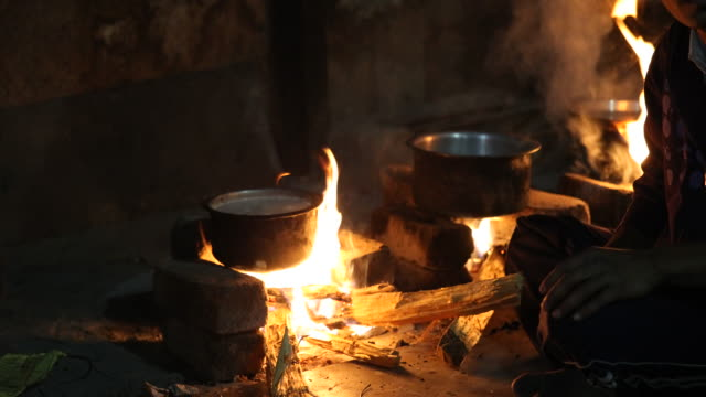 Close up on a man cooking over an open fireplace showing three pots with something boiling and the hand of the man stirring with a wooden spoon