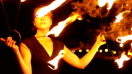 Close up on female holding fire fan and performing