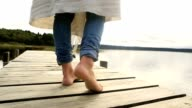 Close up on woman's feet standing on jetty above lake