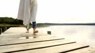 Nahaufnahme der weiblichen Füße stehen auf Steg über dem See