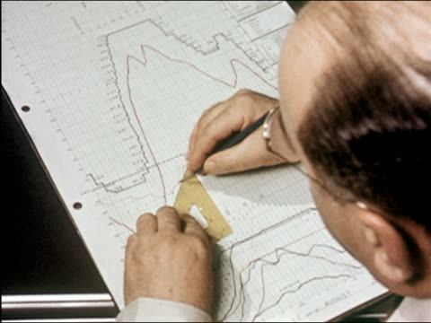 1957 close up over the shoulder of balding man with glasses working on graph w/ protractor at drawing table