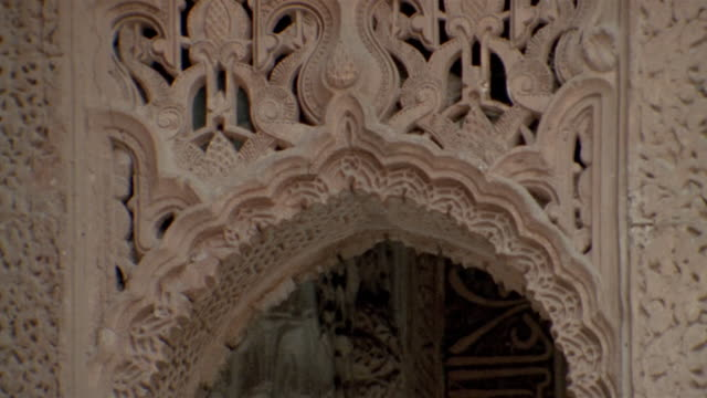 Close up pan archway at Court of Lions/ tilt up details/ tilt down archway/ Alhambra, Spain