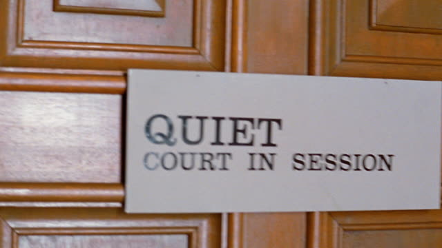 Close up pan bailiff walking through door with 'Quiet court in session' sign