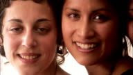 Close up pan faces of three women smiling