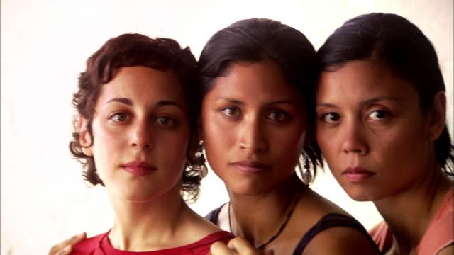 Close up pan faces of three women
