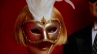 Close up pan from woman in mask to senior man in morning suit and mask posing