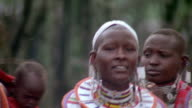 Close up pan group of Masai women and girls in tribal ornaments singing + dancing / South Africa