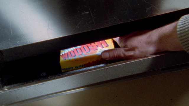 Close up pan hand pulling laundry detergent box from vending machine tray