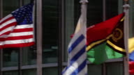 Close up pan international flags waving in wind at United Nations / New York City