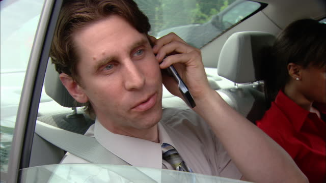 Close up pan man in backseat of car talking on cell phone / pan to woman next to him