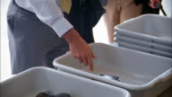 Close up pan people putting belongings into plastic trays at airport security screening station