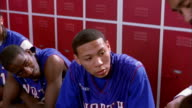 Close up pan teenage basketball players listening to coach in locker room